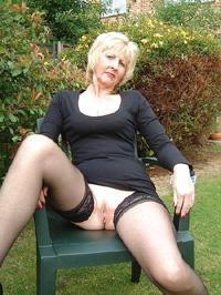 Ältere Blondine ohne Slip im Garten