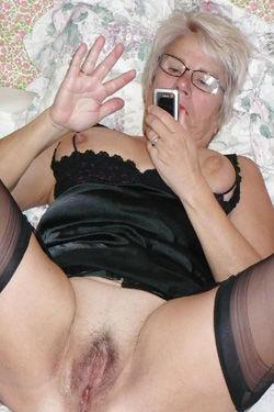 Reife Frau nackt mit einem Handy
